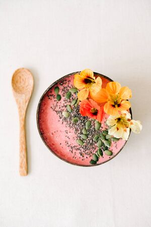 Breakfast in a plate of coconut with nasturtium flowers, Chia seeds and pumpkin seeds