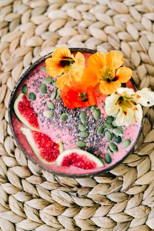 Breakfast in a plate of coconut with nasturtium flowers on natural wicker napkin 写真素材
