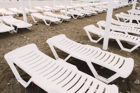 white sunbeds with colorful umbrellas on a pebble beach