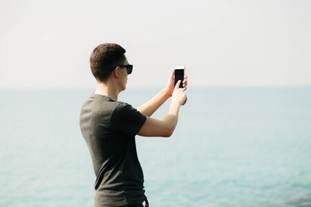 a young guy in a t-shirt and shorts on large rocks, taking pictures of a picturesque place on the sea coast on a smartphone. summer