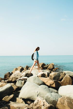 a young girl traveler with a backpack walks barefoot on large stones on the sea coast. summer