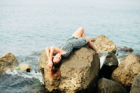 a young girl in a dress on large stones, a picturesque place on the sea coast. summer