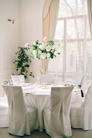 floral decoration of wedding tables, delicate white flowers and branches of fresh greenery
