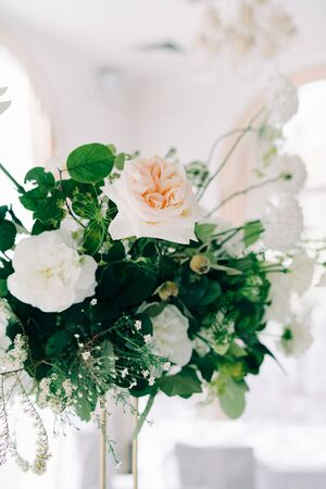 beautiful floral arrangement of delicate rose flowers and fresh greenery in the design of the wedding table
