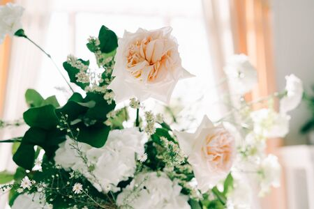 wunderschönes Blumenarrangement aus zarten Rosenblüten und frischem Grün im Design der Hochzeitstafel Standard-Bild