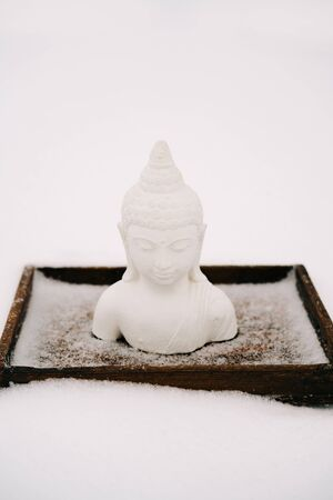 white Buddha figurine made of plaster on a wooden stand during a snowfall