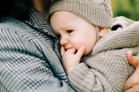 mom holds a little cute boy in a warm jumpsuit, kisses on the cheek in the Park in a clearing strewn with autumn leaves Zdjęcie Seryjne