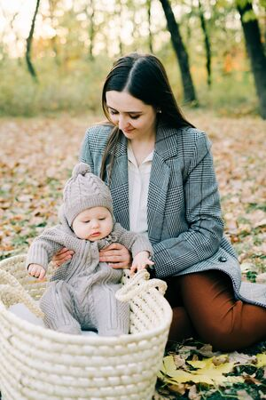 a mother holds a cute little boy in a warm jumpsuit in the Park in a clearing strewn with autumn leaves, in the autumn time Zdjęcie Seryjne
