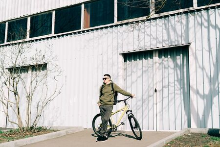 a young man in khaki sportswear holds a Bicycle standing next to him, against the background of a light hangar