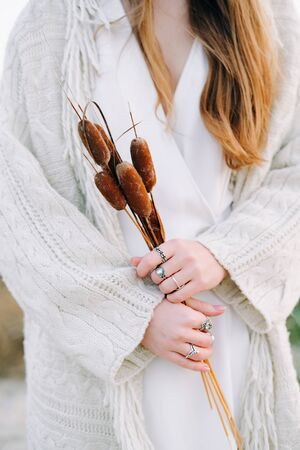 a girl in a white dress, a warm knitted cardigan holds beautiful brown branches of reeds in the autumn period