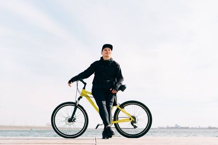 a young man in black sportswear stands on a pontoon near the lake and holds a yellow Bicycle near him Reklamní fotografie