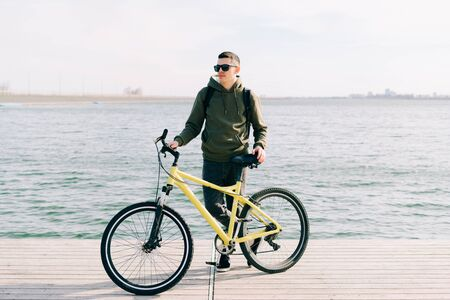 a young man in khaki sportswear and glasses stands on a pontoon near the lake and holds a yellow Bicycle near him