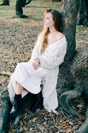 portrait of a young attractive blonde girl in a light white dress and black shoes stands on the root of a tree