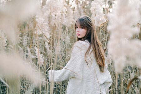 portrait of a young beautiful girl in a white dress, a warm knitted cardigan and black shoes among dry fluffy reeds