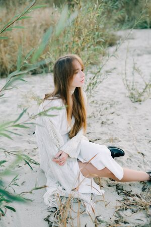 portrait of a young girl in a white dress, a warm knitted cardigan and black shoes among dry reeds and green bushes on the Bank of a river with white sand