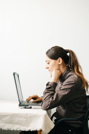 a young European woman, working from home during the virus quarantine, on her laptop. The girl is sitting at a white table, in a minimalistic interior.A cosy working place,the concept of remote work,