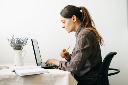 a young woman who works from home while the virus is quarantined on her laptop, studies information on the Internet and writes notes in a diary.A cosy working place,the concept of remote work