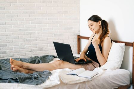 European woman, using a laptop, studying information on the Internet in her bed, writes notes in her diary,while the virus is quarantined.Cozy workplace, e-learning concept