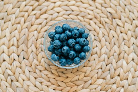 fresh ripe blueberries in a glass bowl on a natural wicker napkin made of dry seaweed on background. the concept of healthy food