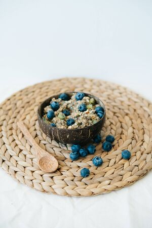oatmeal porridge in bowl with fresh blueberries.Healthy vegan Breakfast cereals, against background of brown natural seaweed napkin and natural wooden bamboo spoon.Concept of clean food
