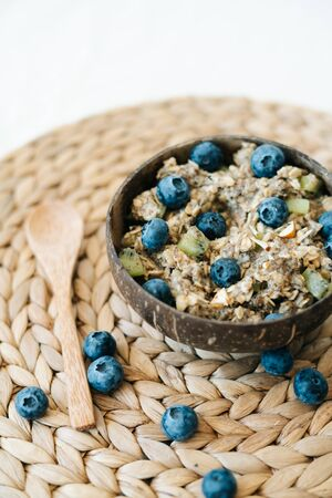 oatmeal porridge in a bowl with fresh blueberries. Healthy vegan Breakfast cereal,on a background of natural brown napkins from the dry algae. Concept of clean food, healthy lifestyle