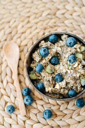 oatmeal porridge in a bowl with fresh blueberries. Healthy vegan Breakfast cereal,on a background of natural brown napkins from the dry algae. Concept of clean food, healthy lifestyle Banque d'images