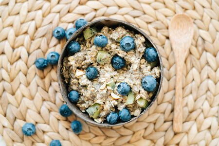 oatmeal porridge in a bowl with blueberries and Chia seeds. Healthy Breakfast cereal, oatmeal cereal with fresh blueberries on a brown background of natural soft dried seaweed. Concept of clean food