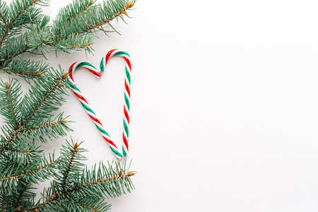 Christmas or new year's background, plain composition of Christmas candy and fir branches, Flatlay, empty space for greeting text.