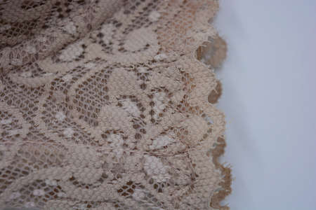 Beautiful attractive beige lace, elegant and unusual fabric is located on a white background.