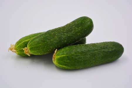 Young juicy cucumbers, Ukrainian cucumber harvest arranged on a white background. Fresh vegetables, healthy food for every day.