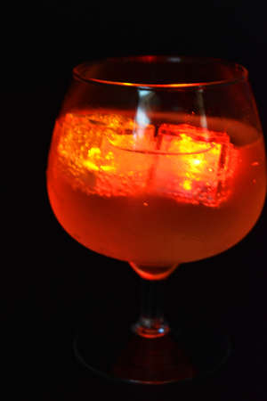 Red bright glowing ice cubes that float in a delicious frosted white cold drink are located in a cognac glass on a black frosted background.