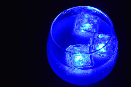 Blue bright glowing ice cubes that float in a delicious frosted white cold drink are located in a cognac glass on a black frosted background. Reklamní fotografie
