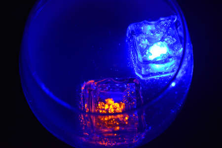 Blue and yellow bright glowing ice cubes that float in a delicious frosted white cold drink are located in a cognac glass on a black frosted background. Reklamní fotografie