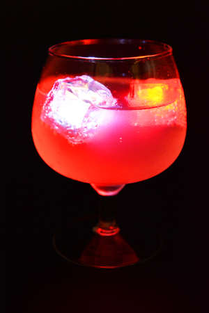 White and red bright glowing ice cubes that float in a delicious frosted white cold drink are located in a cognac glass on a black frosted background.