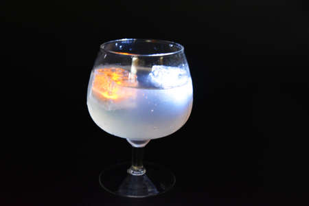 White and yellow bright glowing ice cubes that float in a delicious frosted white cold drink are located in a cognac glass on a black frosted background. Reklamní fotografie