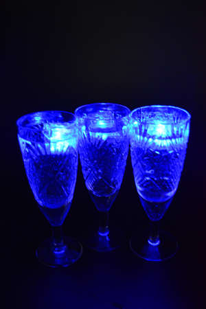 Crystal champagne glasses with carvings in the form of snowflakes are located on a black matte background. Bright multicolor doidic glowing ice cubes float in the drink.