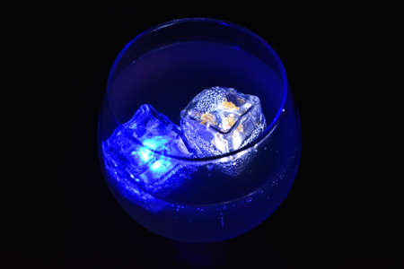 Blue and white bright glowing ice cubes that float in a delicious frosted white cold drink are located in a cognac glass on a black frosted background.