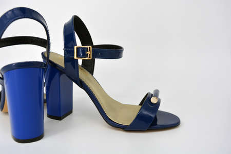 One thing, one pair of female blue lacquer sandals on a wide heel with a golden insole located on a white background.