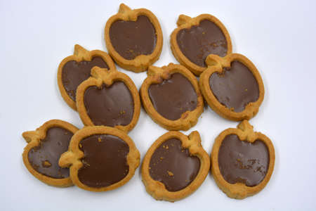 Delicious and sweet shortbread apple-shaped cookies with brown chocolate nut filling located on a white background.