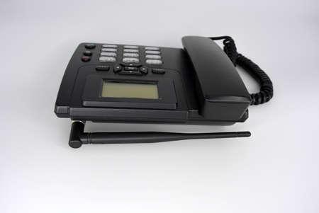 Stationary black plastic radio telephone, telephone with screen, tube and screwed cord.