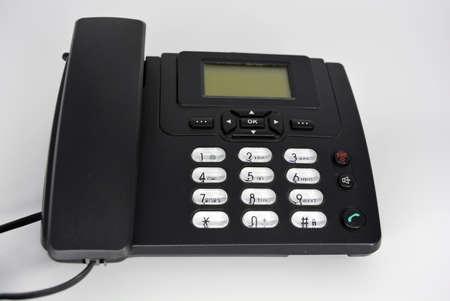 Stationary black plastic radio telephone, telephone with screen, tube and screwed cord. Stock Photo
