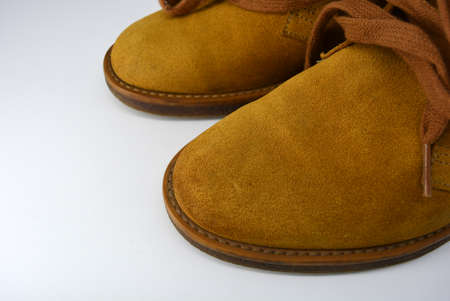 Casual, universal ordinary shoes for a daily walk. Brown half boots, shoes on a wide beige cachic sole. Footwear made of genuine leather, natural suede with brown wide shoelaces.