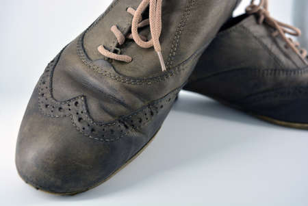 Female leather shoes located on a white background. Oxford shoes with gray shoelaces on a flat heel. Gray women's shoes in a fastening, unwitting.