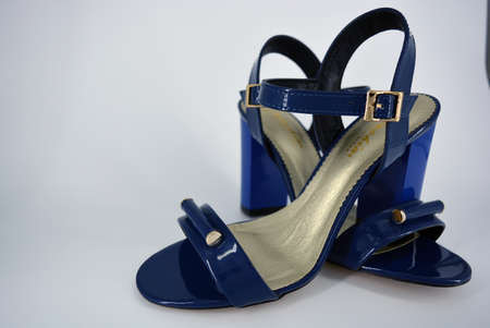 Beautiful and bright female blue lacquer sandals made of genuine leather on a wide heel with a golden insole located on a white background. Stock Photo
