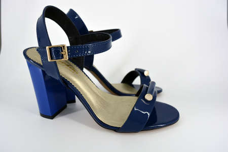 Beautiful and bright female blue lacquer sandals made of genuine leather on a wide heel with a golden insole located on a white background.