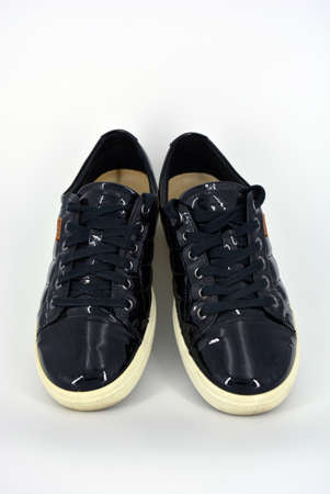 Stylish bright black lacquer shoes located on a white background. Moccasins made of genuine leather with bullshit and black wide laces. Women's sneakers on a white tast sole.