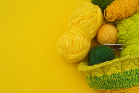 Yellow and green coats of wool lie on the table. Favorite hobby is knitting. Home cosiness. Stock Photo