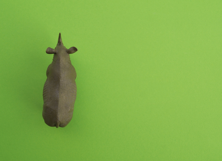 An rhinoceros animal is a childrens toy. Plastic figurine for the game. Green background. Farm and the zoo.
