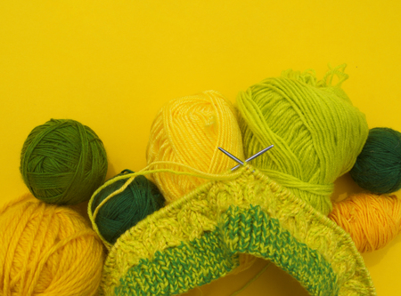 Yellow and green coats of wool lie on the table. Favorite hobby is knitting. Home cosiness. Standard-Bild