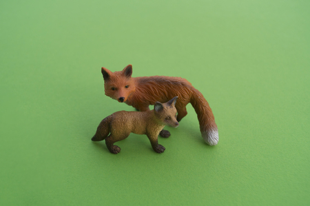 An fox animal is a children's toy. Plastic figurine for the game. Green background. Farm and the zoo. Stock fotó